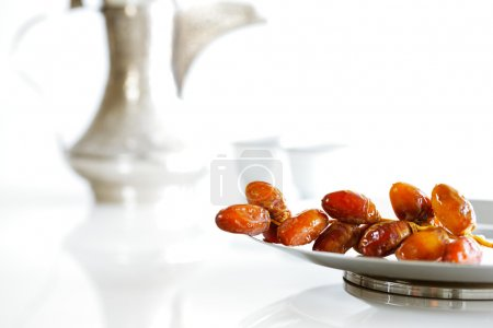Arabic dates on a plate with Arabic coffee pot of the Bedouin
