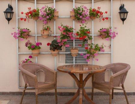 Photo pour Chaises en osier et une table sur la terrasse avec des fleurs - image libre de droit
