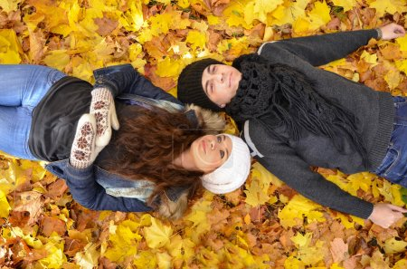 Young couple relaxing on autumn leaves