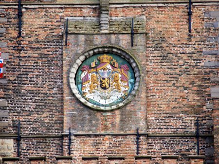 Coat of Arms on a brick wall of Tower belfry Belfort