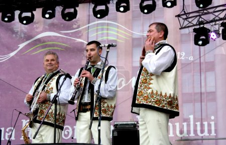 Wind instruments performers have fun playing music in the Moldovan national costumes