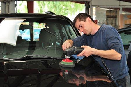 Worker polishing a car bonnet.