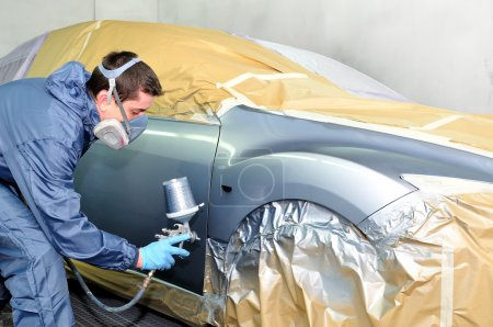 Photo for Worker painting a car in paint booth. - Royalty Free Image
