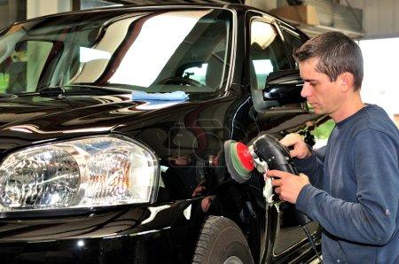 Worker polishing a car.