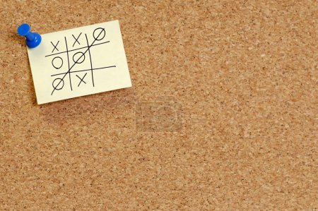 Game of tic tac toe on note on corkboard