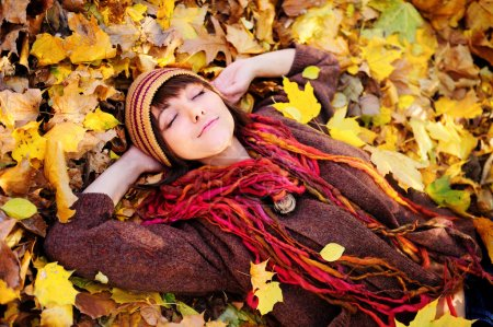 Girl portrait lying in leaves.
