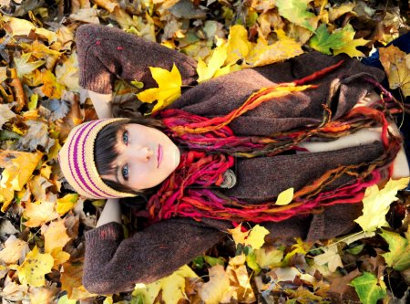 Photo for Girl lying in autumn yellow leaves. Outdoor. - Royalty Free Image