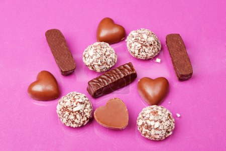 Photo for Assorted chocolate pralines on pink background - Royalty Free Image