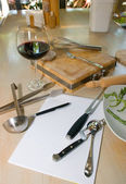 Utensils, notebook and glass of wine