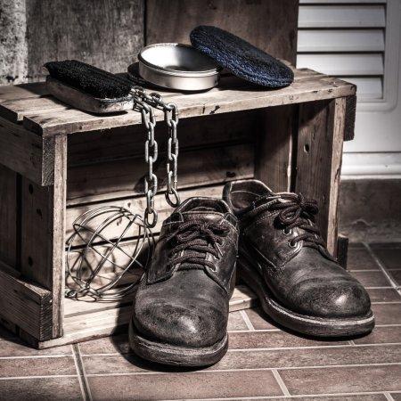 Foto de Zapatos resistentes en caja de madera con set de limpieza y cadena, todavía luz - Imagen libre de derechos
