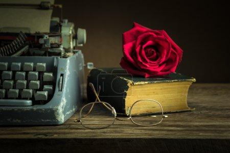 Foto de Bodegón con capullo de rosa roja en viejo libro junto a la máquina de escribir y gafas - Imagen libre de derechos