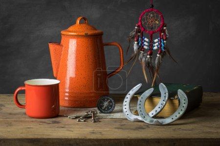 Photo pour Nature morte avec capteur de rêves, fers à cheval, carte, boussole et vieux livre - image libre de droit