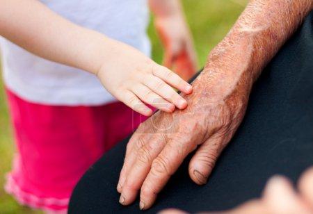 Photo pour Une petite fille touchant doucement la main de sa grand-mère . - image libre de droit