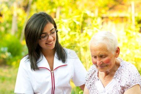 Helping elderly woman outdoors