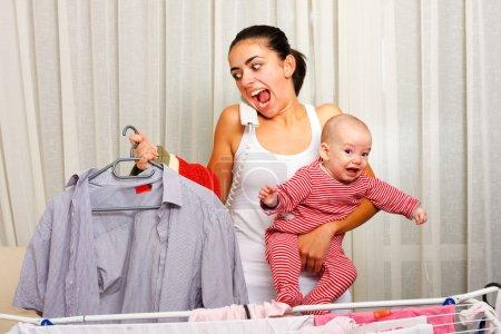 Photo pour Crier jeune mère en a marre de faire la lessive, tenant son enfant en pleurs et parlant au téléphone en même temps . - image libre de droit