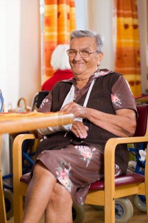 Photo pour Une femme âgée aux bras cassés souriant, assise sur une chaise dans une maison de retraite - image libre de droit
