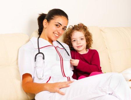 Photo pour Petite fille souriante assise à côté de la gentille infirmière . - image libre de droit