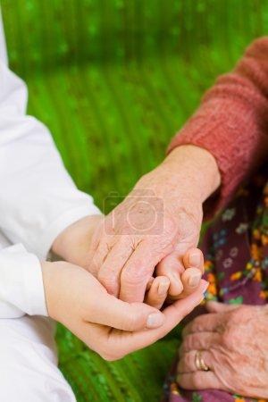 Photo pour Un jeune médecin tenant la main d'une vieille femme - partie d'une série . - image libre de droit