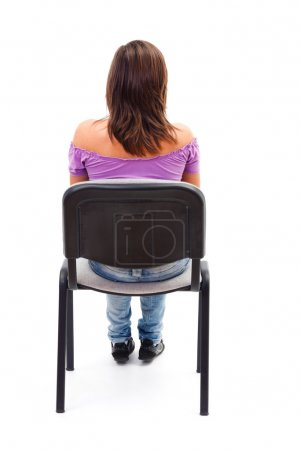 Photo for A young woman / girl sitting on a chair looking forward with her back facing to the camera. - Royalty Free Image