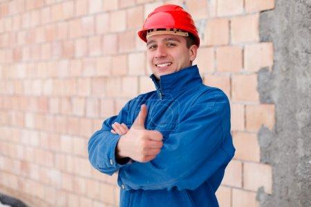 Photo pour Travailleur de la construction heureux montrant vignette à côté d'un mur de briques inachevé . - image libre de droit