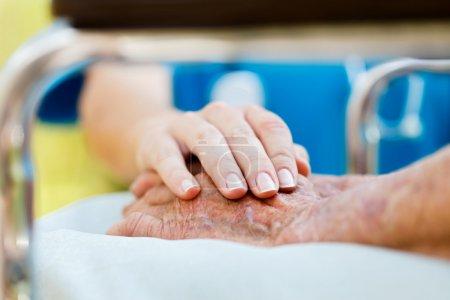 Photo pour Médecin soignant ou infirmière tenant les mains d'une dame âgée en fauteuil roulant . - image libre de droit