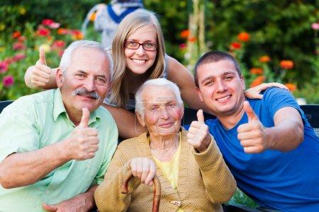 Photo pour Famille heureuse et satisfaite montrant thumbsup pour la qualité de la résidence entretien de grand-mère. - image libre de droit
