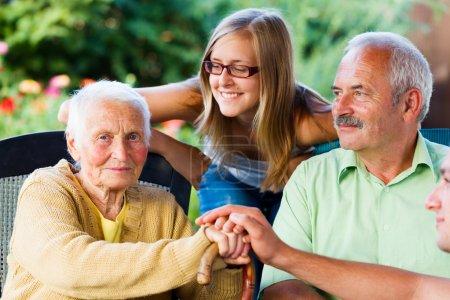 Photo pour Femme âgée se félicitant de sa famille - fils et sa petite-fille dans le jardin de la maison de retraite. - image libre de droit