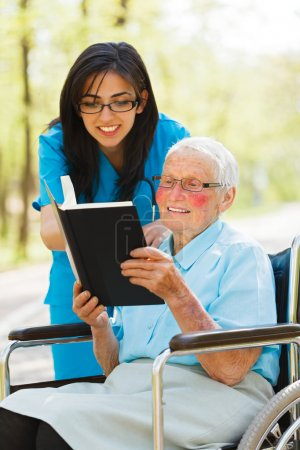 ältere Dame im Rollstuhl liest