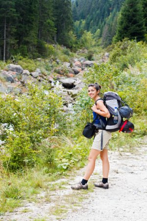 Photo for Hiking lady with big backpack going to a journey in the mountains. - Royalty Free Image