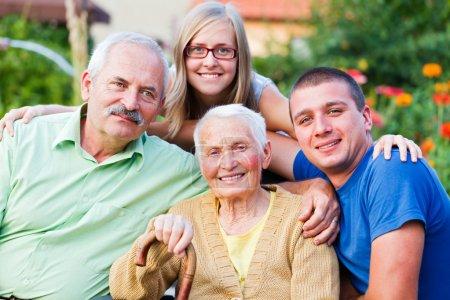 Photo pour Générations en une seule image : petits-enfants de grand-mère, les fils et les jeunes dans le jardin de la maison de retraite. - image libre de droit