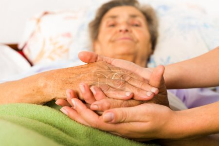 Photo for Caring nurse holding kind elderly lady's hands in bed - Royalty Free Image