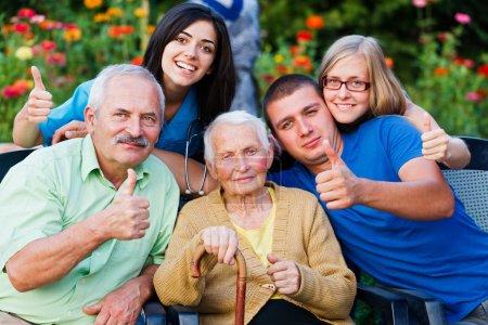 Photo pour Groupe heureux de personnes - famille et médecin - montrant thumbsup pour les services de haute qualité dans la maison d'habitation - image libre de droit