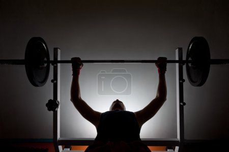 Photo for Man weightlifter at the gym, lifting weights on a benchpress - Royalty Free Image