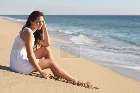 Photo for Beautiful woman thinking and watching the sea on the beach - Royalty Free Image