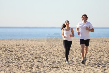 Photo for Man and woman running in the beach smiling - Royalty Free Image