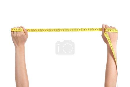 Photo pour Belle main de femme étirant une bande de mesure sur un fond isolé blanc - image libre de droit