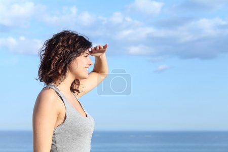 Photo for Beautiful woman looking forward with the hand in forehead and the sea in the background - Royalty Free Image