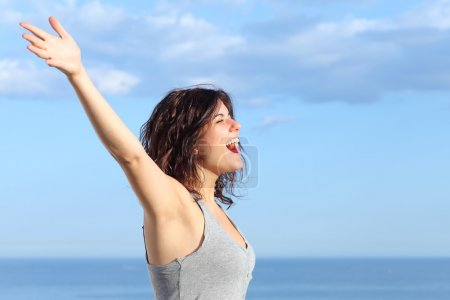 Attractive woman with raised arms shouting to the wind