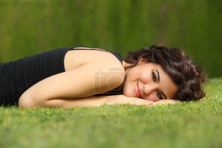 Beautiful woman lying on the grass relaxed