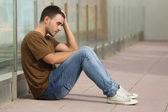 Dospívající chlapec obává, sedí na podlaze