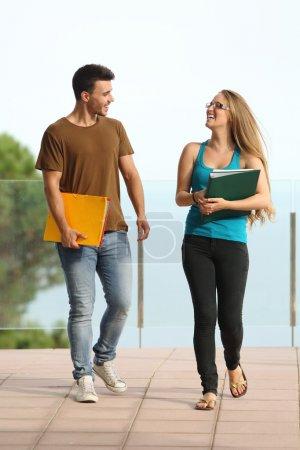 Teenager students boy and girl walking towards camera