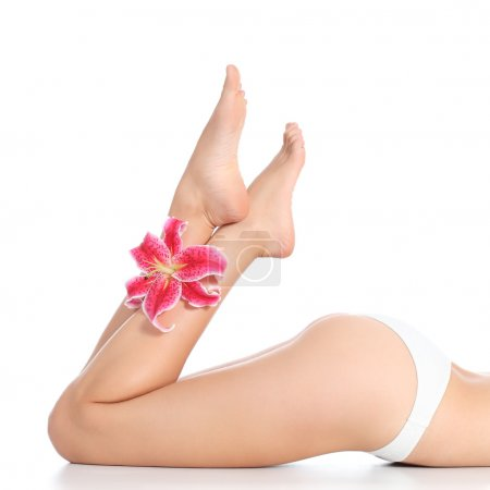 Beautiful smooth and waxed woman legs and feet with a flower