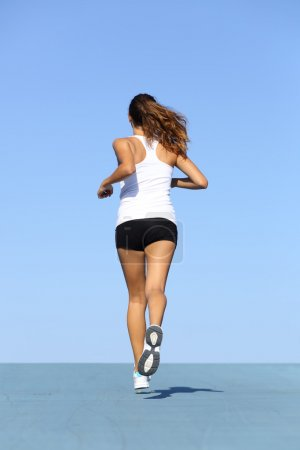 Photo for Back view of a fitness woman running on blue with the horizon in the background - Royalty Free Image