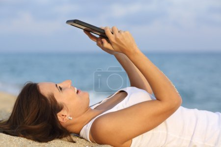 Side view of a teenager girl browsing her tablet pc lying on the sand of the beach