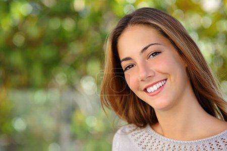 Photo pour Belle femme du visage avec un sourire blanc parfait en plein air avec un fond vert - image libre de droit