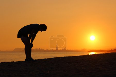 Silhouette of an tired sportsman at sunset with a ...