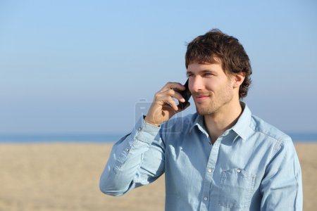 Attractive man talking on the phone on the beach