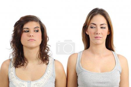 Photo pour Deux filles à la recherche de l'autre en colère isolé sur fond blanc - image libre de droit