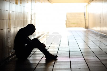 Photo for Backlight of a teenager depressed sitting inside a dirty tunnel - Royalty Free Image