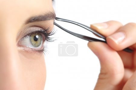 Photo for Close up of a woman eye and a hand plucking eyebrows isolated on a white background - Royalty Free Image